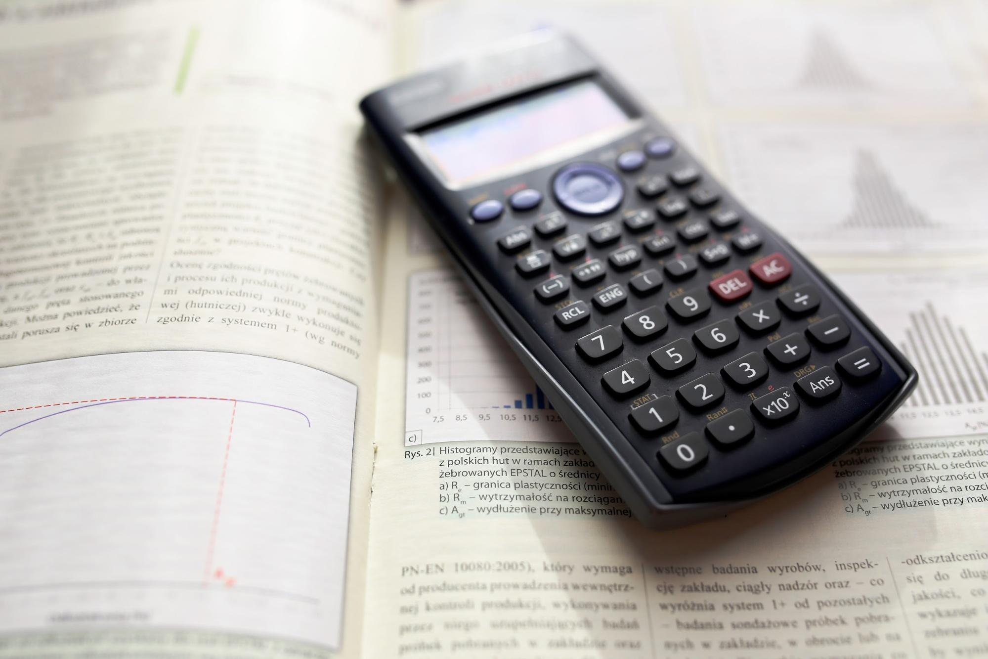 Close up of a calculator sitting on top of a textbook