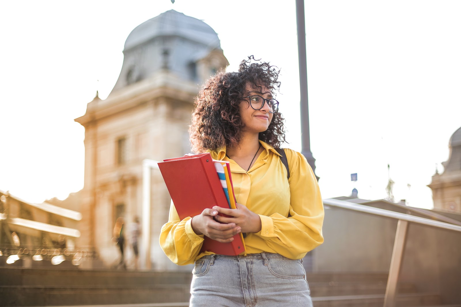 Woman in yellow shirt holding binder and books
